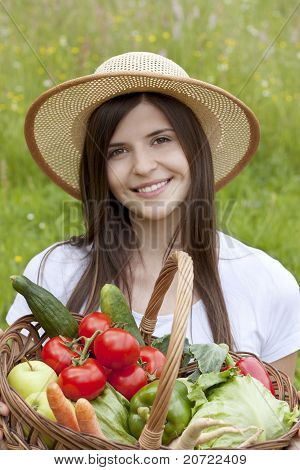 Portrait Of A Pretty Teenage Girl Holding A Basket Of Vegetables