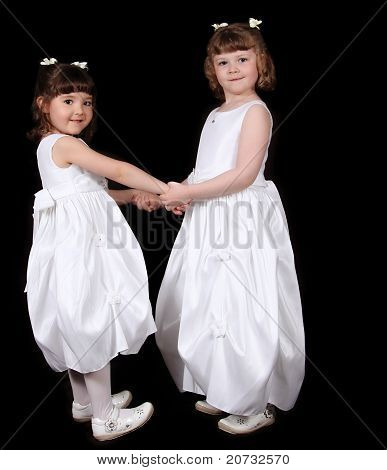 Adorable Twin Sisters In White Gowns Haolding Hands. Isolated On