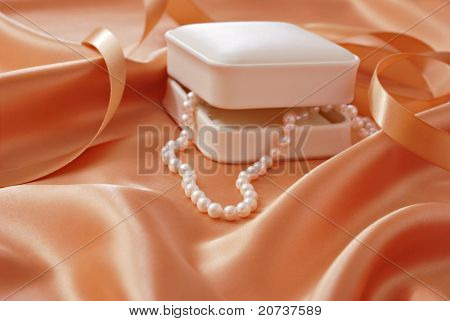 Beautiful cultured pearls cascading from jewelry gift box onto peach colored satin.  Macro with extremely shallow dof.  Selective focus limited to closest pearls.