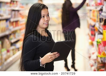 Young woman looking at the products while using digital tablet in shopping centre with person in the background