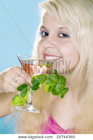 nice blonde girl  holds in hand glass and  mint