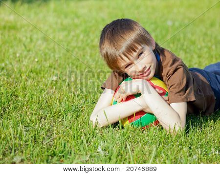 Cute boy lying on grass with soccer ball