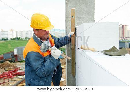 construction mason worker bricklayer installing calcium silicate brick by hammer hitting work