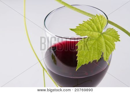 Glass of red wine, with a green leaf