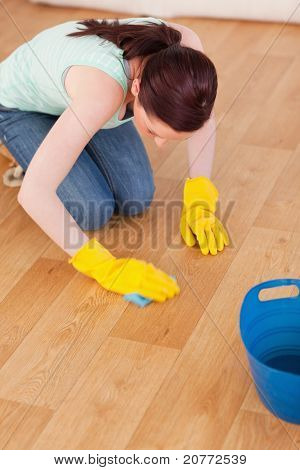Good looking red-haired woman cleaning the floor while kneeling at home