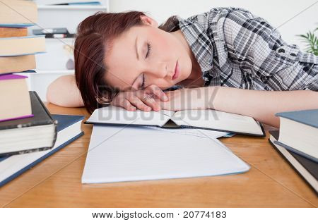 Pretty red-haired girl having a rest while studying at her desk