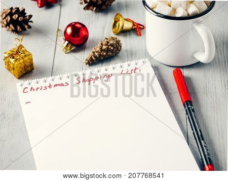 poster of Christmas gifts shopping planning. Make shopping or to-do list for Christmas. Notebook, mug hot chocolate with marshmallows, New Year's decoration and pine cone on gray wooden background.