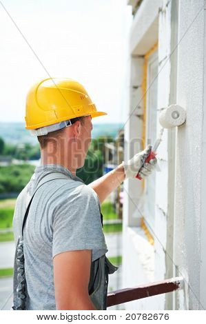 Young painting facade builder worker with roller at thermal insulation works