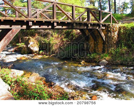 Old Wooden Bridge Over A Stream In A Forest