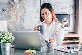 Asian Businesswoman Take A Coffee Break After Working At Laptop Computer On Desk With Smiling Face,h poster