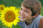 Boy Smiling With A Flower