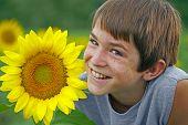 Постер, плакат: Мальчик улыбается с цветком