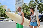 Honolulu Hawaii lifestyle surfers people walking in city with surfboards going to the beach surfing. poster