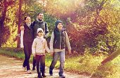 travel, tourism, hike and people concept - happy family walking with backpacks along road in woods poster