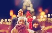 family, holidays and people concept - happy parents with kids outdoors over christmas lights backgro poster