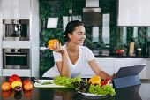 Young Woman Looking At Recipe In Laptop In Kitchen. Healthy Food - Vegetable Salad. Diet. Dieting Co poster