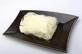 stock photo of pancit  - Dried raw pancit noodles on a brown ceramic dish - JPG