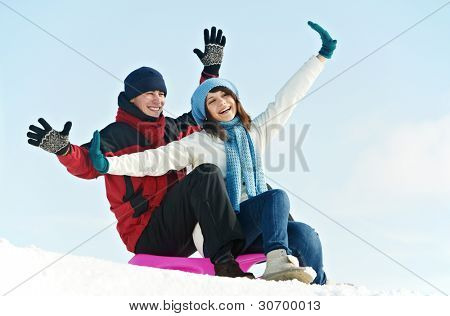 Group of happy young smiling people in warm clothing outwear sitting on sled at winter outdoors over blue sky