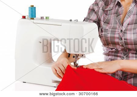 Woman is sewing on the sewing machine