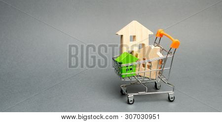 poster of Wooden Houses In A Supermarket Trolley. The Concept Of Buying A House Or Apartment. Affordable Housi