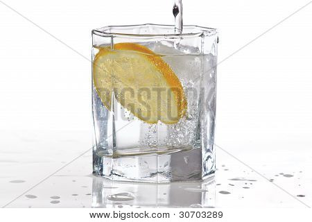 Glass of mineral water, ice and slice of fresh lemon with splash