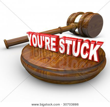 The words You're Stuck on a wooden block with a judge's gavel beside it illustrating that you are on the wrong side of the law or a legal case verdict and are in trouble