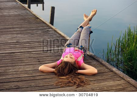 Relaxing young woman lying on the bridge