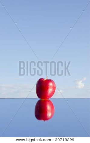 One Red Apple On Mirror And Sky