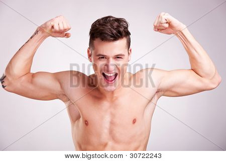 Well-built muscularyoung man with arms raised on studio gray background. model with flexed biceps screaming