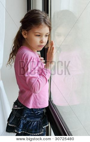 Little beautiful sad girl looks out window and touches glass by hand