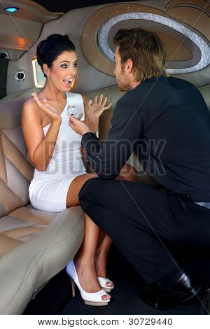 Young man proposing beautiful woman in limousine with engagement ring.?