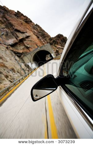 Car Approacting Tunnel Through Mountains