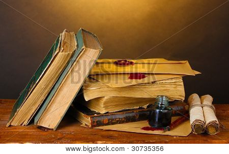 old books, scrolls, ink pen and inkwell on wooden table on brown background