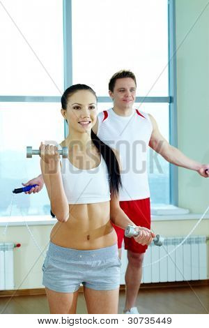 Image of fit woman doing exercise with barbells with young guy on background