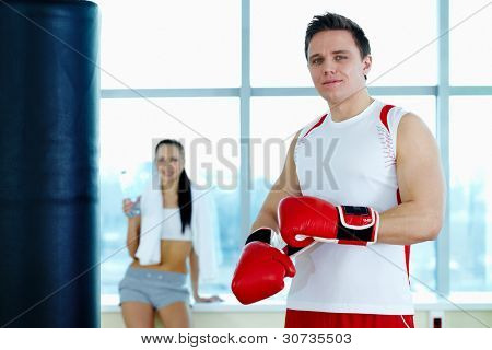 Portrait of young man in red boxing gloves looking at camera in gym
