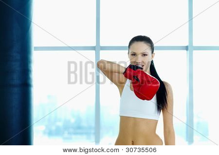 Portrait of young woman in red boxing gloves looking at camera in gym