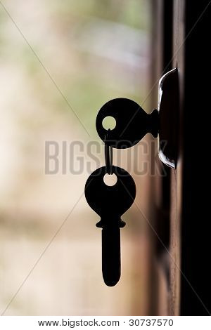 Silhouette Of Door Keys Hanging On The Open Door