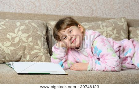 The Little Girl Reads The Book Lying On A Sofa