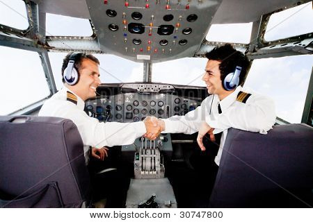 Happy pilots handshaking in the airplane cabin