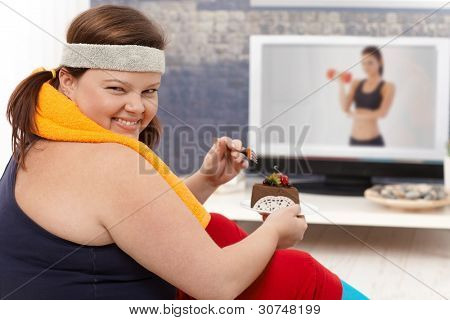 Fat woman choosing chocolate cake instead of doing gymnastics, smiling happily.?