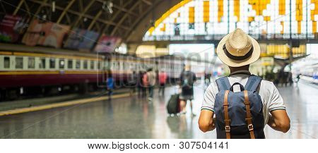 poster of Young Man Traveler With Backpack Waiting For Train, Asian Backpacker With Hat Standing On Railway Pl