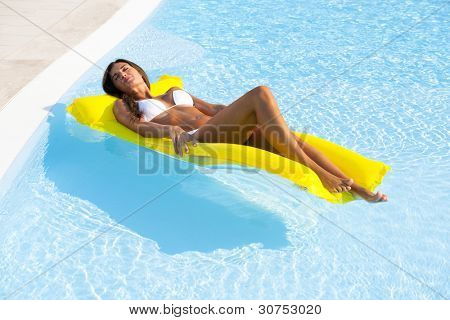 Beautiful woman relaxing and floating on pool, high angle view