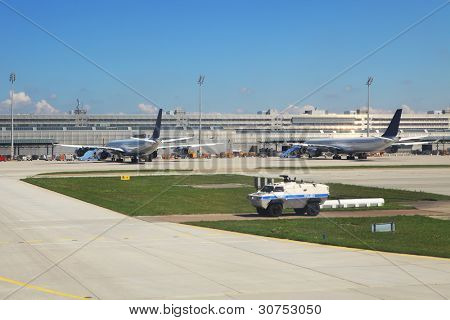 Armored police vehicle secures perimeter and exit to runway and two passenger airliners on the background standing at the gates in Munich International Airport, Germany.