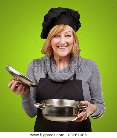 Middle aged cook woman holding a sauce pan over green background