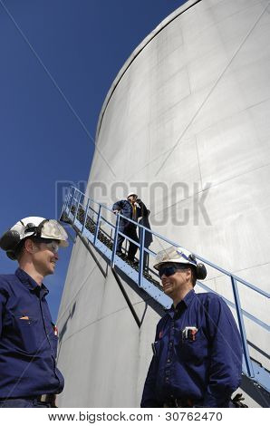 refinery workers with giant fuel storage towers in background