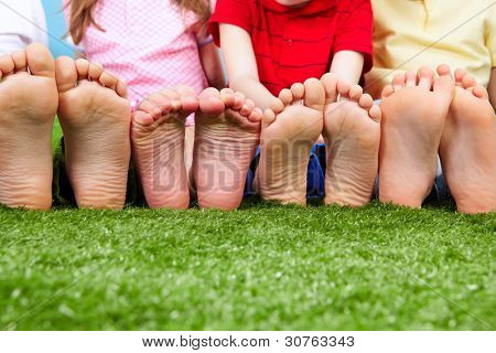 Happy friends sitting on the grass barefoot