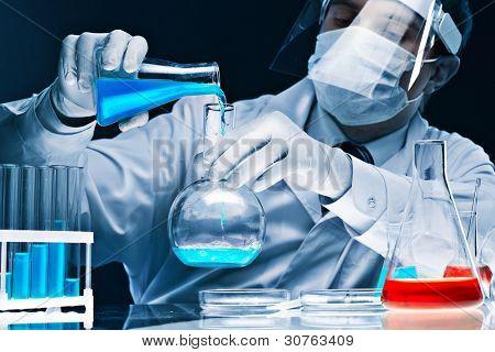 Científico hombre enmascarado mezcla sustancias azules brillantes en cristalería