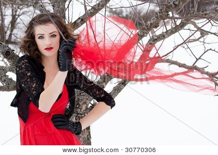 Beautiful Woman With Dark Hair And Red Lips In White Snow