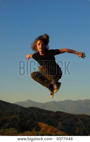 Male Jumping Over Mountain Peaks Agains A Blue Sky