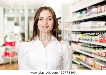 Portrait of a young attractive pharmacist looking at the camera in a pharmacy